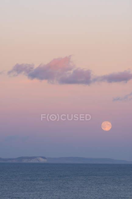 Royaume-Uni, Dorset, pleine lune au coucher du soleil sur l'eau — Photo de stock