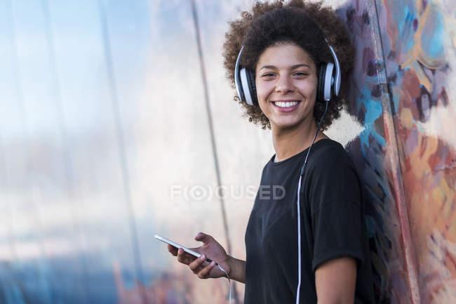 Ritratto di giovane donna felice con cuffie e smartphone appoggiato al muro — Foto stock