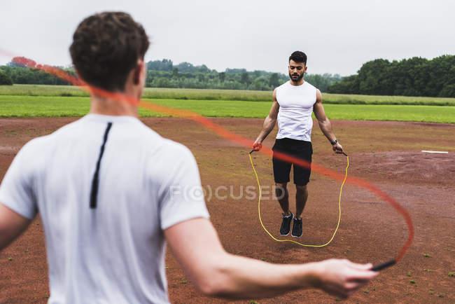 Два спортсменів, пропускаючи мотузку спортивний майданчик — стокове фото