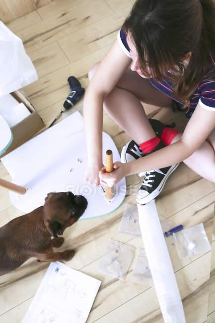 Femme assemblant des meubles flatpack — Photo de stock