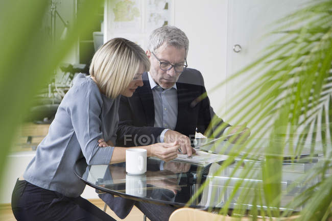 Businessman and businesswoman working together in office and discussing documents — Stock Photo