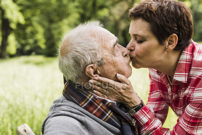 Woman kissing her old father sitting on a bench in nature — Stock Photo