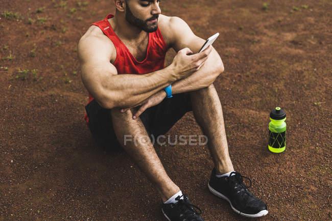 Спортсменка на відкритому повітрі, сидячи на землі, дивлячись на мобільний телефон — стокове фото
