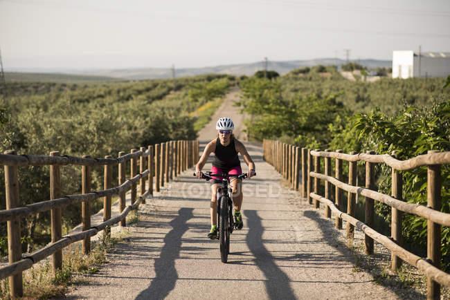 Bicicletas del montar a caballo de atleta en paisaje rural - foto de stock