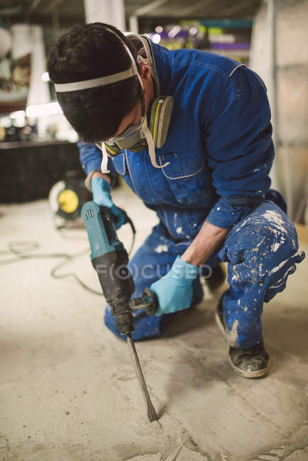 Bricklayer removing irregularities on floor screed with jackhammerac — Stock Photo