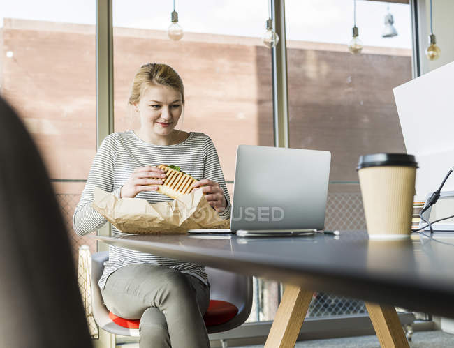 Young woman having lunch break in office — Stock Photo