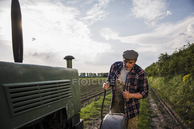 Farmer standing next to tractor at a field — Stock Photo