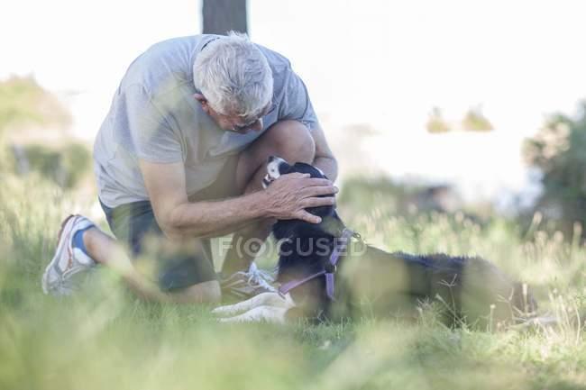 Senior homme caressant son chien outddors — Photo de stock