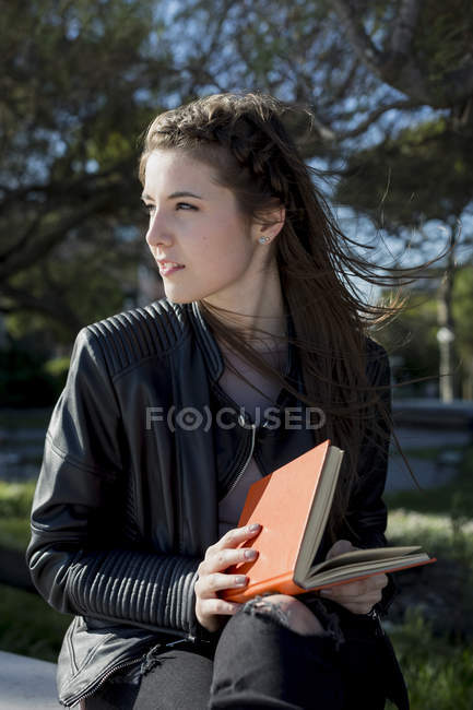Mujer joven en el parque leyendo libro - foto de stock