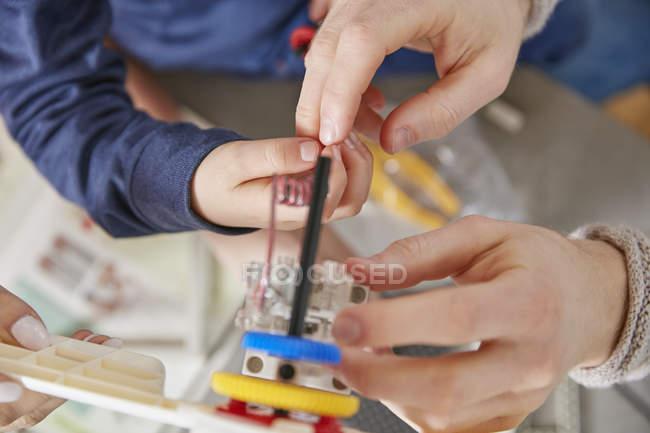 Hands assembling plastic cogwheels — Stock Photo