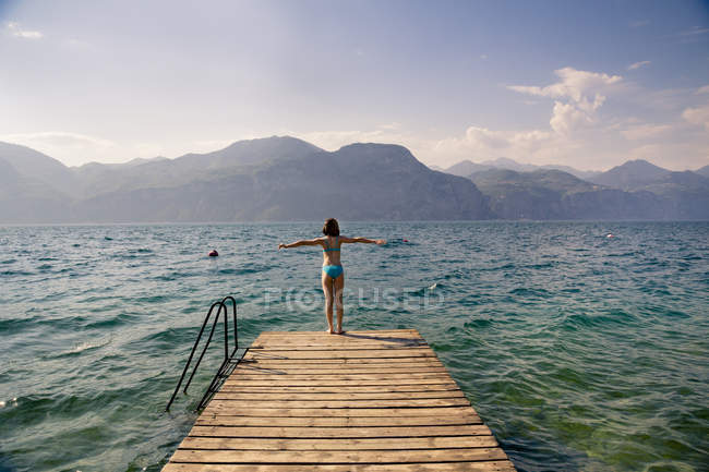 Italy, Brenzone, back view of girl standing on jetty — Stock Photo