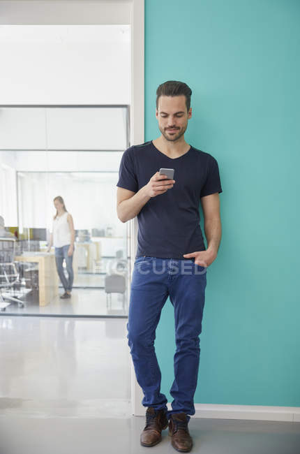 Man standing in office and using smartphone — Stock Photo