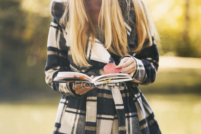 Підлітка дівчинка тримає книгу та Осінні листи — стокове фото