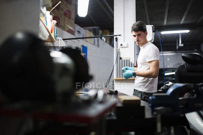 Young Electronic technician repairing in workshop and looking at camera — Stock Photo