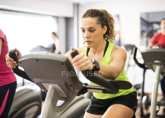 Frau am Heimtrainer im Fitness-Studio trainieren — Stockfoto