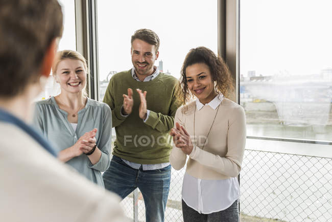 Three smiling colleagues applauding for mature woman in office — Stock Photo