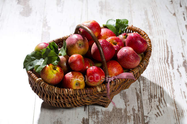 Panier en osier de pommes rouges — Photo de stock