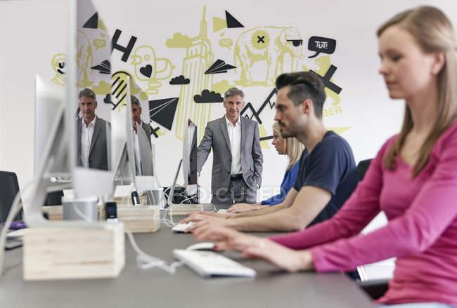 Mature caucasien homme d'affaires regarder collègues — Photo de stock