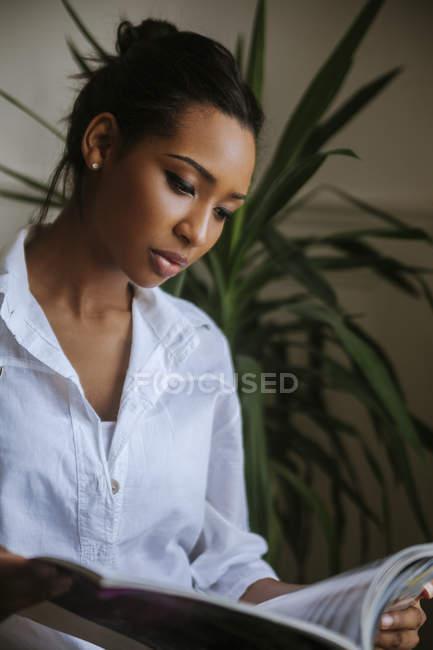 Портрет молодої жінки читання журналу — стокове фото