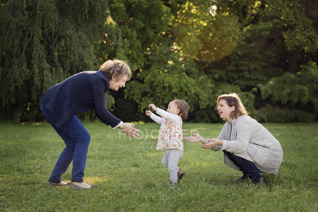 Toddler making first steps between  grandmother and mother in a park — Stock Photo