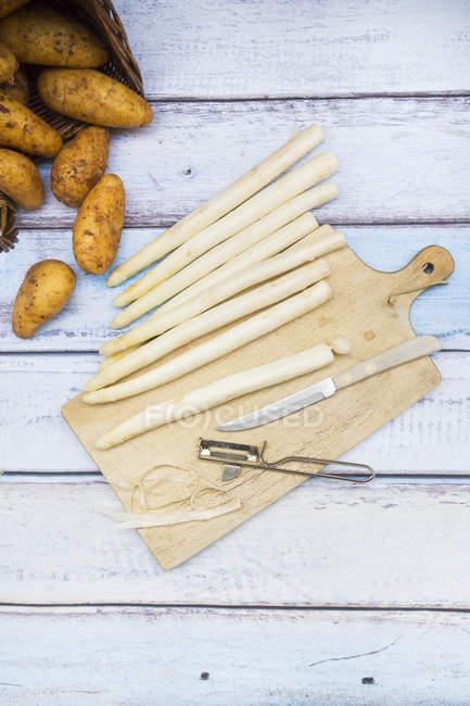 Espárragos blancos con cuchillo y pelador - foto de stock
