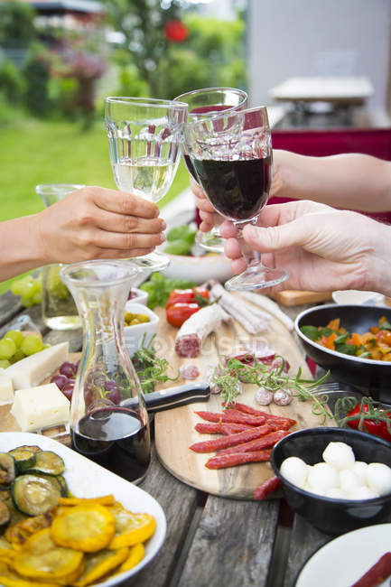 People clinking wine glasses and enjoying variety of Mediterranean antipasti in garden — Stock Photo