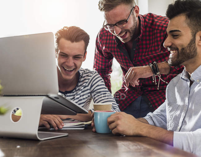 Three happy young professionals sharing laptop in office — Stock Photo