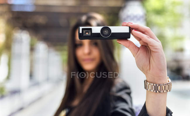 Young woman taking a picture with an old camera — Stock Photo