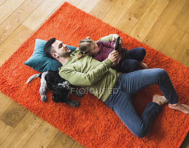 Père et fille couché sur le tapis sur le sol à l'aide de tablette numérique — Photo de stock