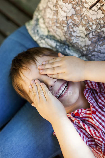 Little boy lying on mother's lap covering eyes with his hands — Stock Photo