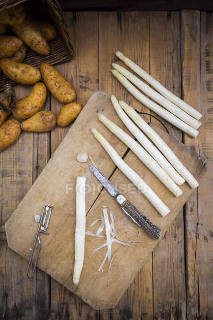 Espargos brancos com faca e descascador — Fotografia de Stock