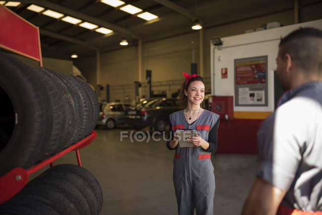 Mechanic checking tires and wheels in workshop — Stock Photo