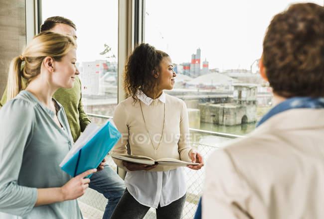Colleghi in ufficio guardando fuori della finestra sorridenti — Foto stock