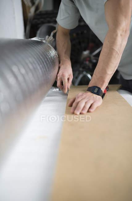 Junger Mann schneiden ein isolierendes Material für einen Laminatboden — Stockfoto
