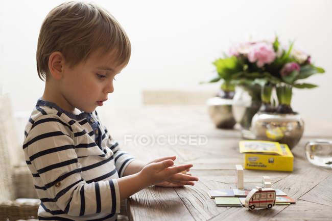 Маленький хлопчик грає за обіднім столом з іграшками — стокове фото