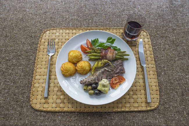 Filet d'agneau avec croquettes, haricots verts enrobés de bacon, artichaut, tomate et piment, verre de vin rouge — Photo de stock