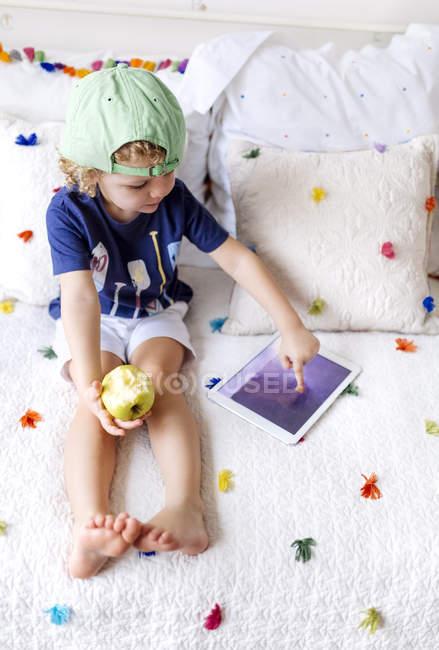 Menino sentado no sofá com uma maçã usando tablet digital — Fotografia de Stock