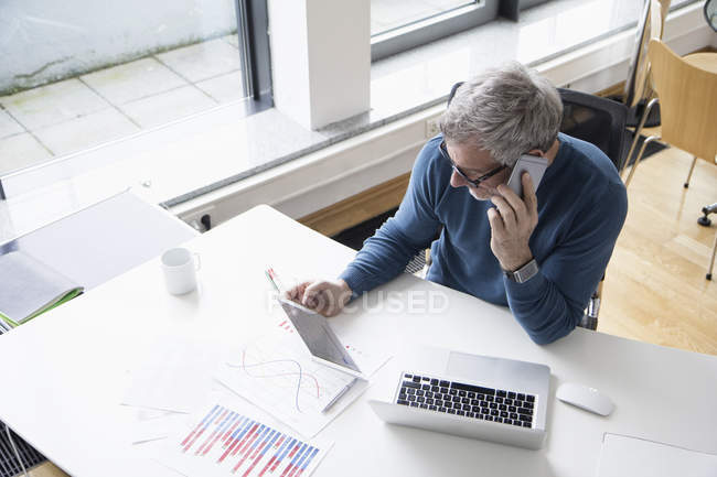 Mature man working in office with smart phone and digital tablet — Stock Photo