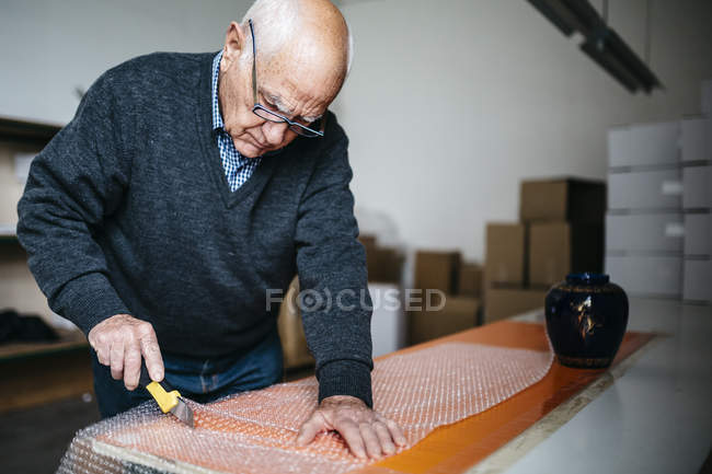 Senior man wrapping the finished ceramic piece — Stock Photo