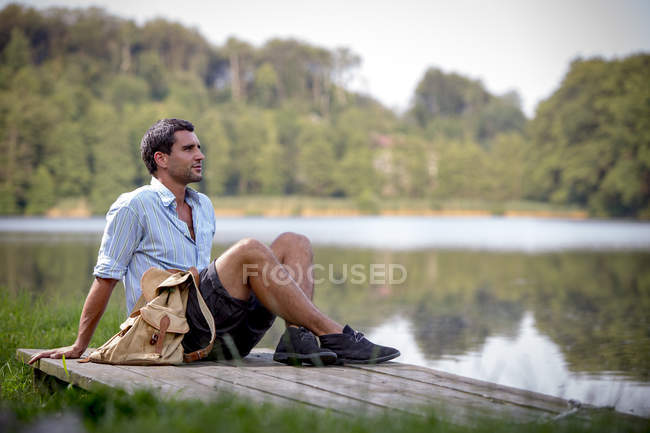 Retrato de um jovem sentado em um molhe no lago — Fotografia de Stock