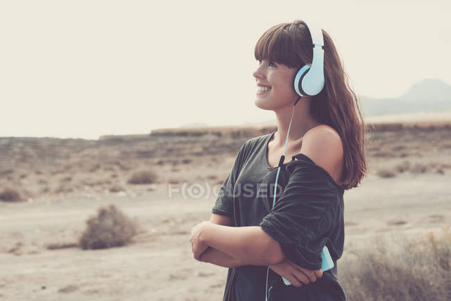 Young woman listening music, smiling happily — Stock Photo