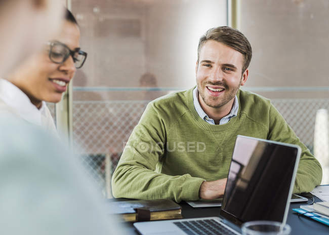 Colleagues in office with laptop having a meeting — Stock Photo