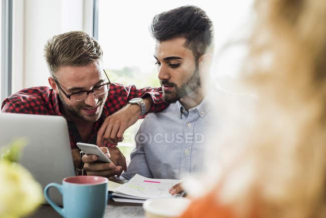 Junge Berufstätige schauen im Büro aufs Handy — Stockfoto