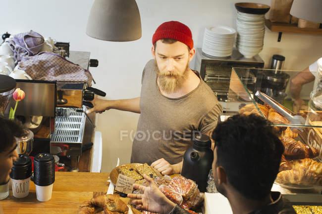 Man talking to barista at cafe counter — Stock Photo