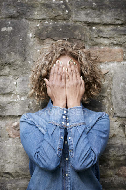Woman covering face with her hands — Stock Photo