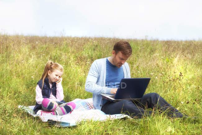 Pai e filha sentados no prado, smartphone e laptop — Fotografia de Stock