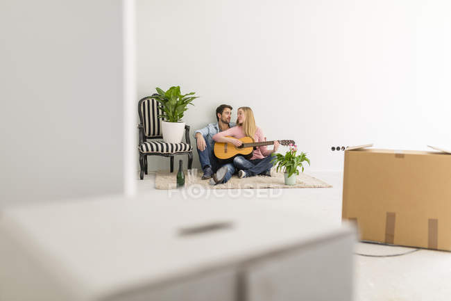 Happy couple sitting on the floor of their new home playing guitar and singing together — Stock Photo