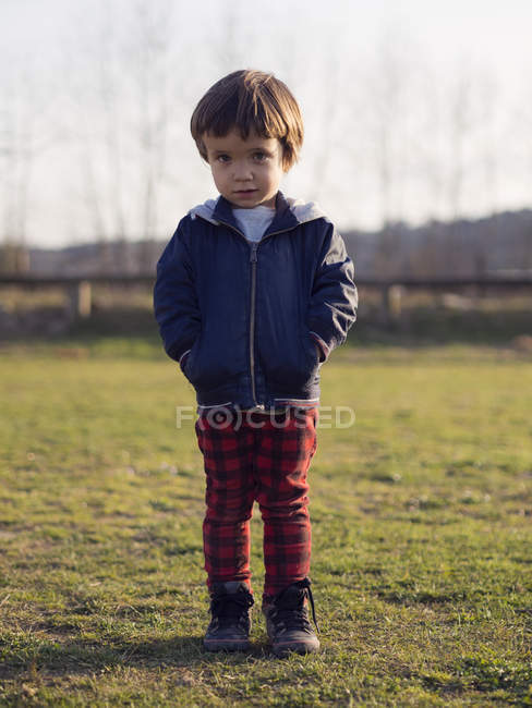 Little boy standing on grass with hands in pockets looking at camera — Stock Photo