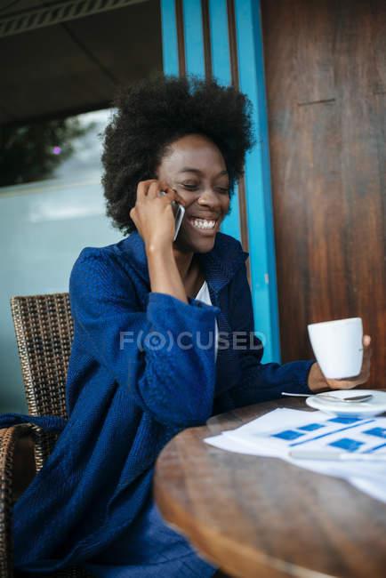 Портрет молодой женщины, разговаривающей по мобильному телефону и пьющей кофе в уличном кафе — стоковое фото