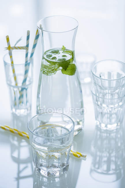 Glass bottle of water flavored with lemon balm and different glasses — Stock Photo